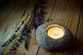 Stone candle holder with tea light on barn wood, lavender twigs, Easter, tranquility Royalty Free Stock Photo