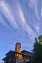 Stone chimney against blue sky with wispy clouds