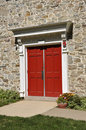 Stone church and red doors Royalty Free Stock Images