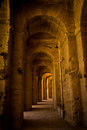 Stone corridor inside the coliseum with columns and sunlight Royalty Free Stock Photo