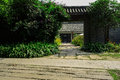 Stone and crosstie paved path at gate of traditional Chinese yar Royalty Free Stock Photo