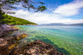 Stone crystal clear tourquise sea surrounding by pine trees in Croatia, Istria, Europe Royalty Free Stock Photo