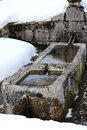Stone fountain with freezing cold water in winter Royalty Free Stock Photo