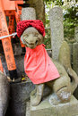 Stone fox statue with red cap. Royalty Free Stock Photo
