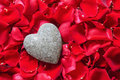 Stone heart in rose petals a lies a bed of red Royalty Free Stock Photos