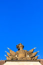 Stone knight armor statue on a roof under blue sky with flags and spears in the back the Royalty Free Stock Image