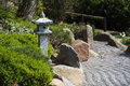 Stone lantern between evergreen plants, rocks and raked gravel, Royalty Free Stock Photo