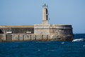 Stone lighthouse over ocean and blue sky old small Royalty Free Stock Photo