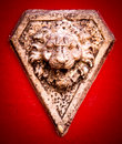 Stone lion head in a red wall Royalty Free Stock Image