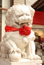 Stone lion with a red bow in a street of Beijing Royalty Free Stock Photos