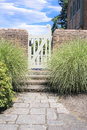 Stone path to garden gate natural backyard with brick wall Royalty Free Stock Photography