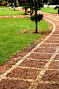 Stone pathway trails in the park with green grass background Royalty Free Stock Images
