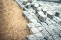 Stone pavement, construction worker laying cobblestone rocks on sand Royalty Free Stock Photo