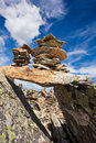Stone pile on mountain many small piles peak with blue sky and clouds close up Stock Photography