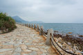 Stone road and sea with fence next to a under cloudy sky Stock Photos