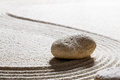 Stone on sinuous lines for harmony or progression on sand zen still life single set concept of with care closeup Stock Images