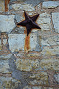 Stone slab wall with star a background a rusty hanging on it Stock Image