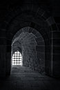 Stone wall with a backlit window with iron grid at an old citadel in Alexandria, Egypt Royalty Free Stock Photo