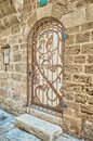 Stone wall. a beautiful door with a pattern behind an iron grating. Israel Royalty Free Stock Photo