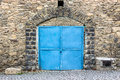 Stone wall with blue door arch and metall Stock Photos