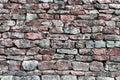 Stone wall closeup, horizontal stonewall pattern background, old aged weathered red and grey grunge limestone dolomite slate slab Royalty Free Stock Photo