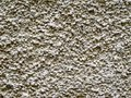 Stone wall gray plastered with grained texture useful as background Royalty Free Stock Image