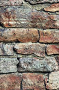 Stone wall macro closeup, stonewall pattern background, vertical, old aged weathered red and grey grunge limestone dolomite Royalty Free Stock Photo