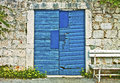 Stone wall, vintage blue gate and wooden bench Royalty Free Stock Photo