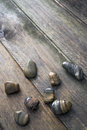 Stone and wood bright pebbles on a rustic wooden surface Stock Image