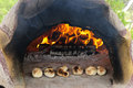 Stone wood oven baking bread with fire fresh homemade Stock Photo