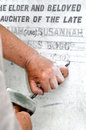 Stonemason engraving marble gravestone using traditional skills to engrave a white Stock Image