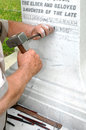 Stonemason engraving marble gravestone using traditional skills to engrave a white Royalty Free Stock Photo