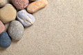Stones background on sandy beach pebbles texture macro shot Royalty Free Stock Image