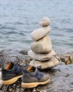 Stones in balance on the rocks of the sea with a pair shoes Stock Photo