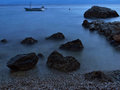 Stones and boat at misty sea view a rocks cliffs blurred little anchored in the adriatic in blue sunset in croatia dalmatia Royalty Free Stock Photo