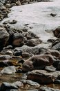 Stones covered with snow and river movement Royalty Free Stock Photo