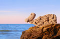Stones duck bird shaped on the top of coastal boulder Stock Photo