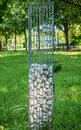 Stones in a metal cage as a decoration for a garden or park Royalty Free Stock Photo