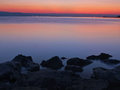 Stones at misty sea view a black rocks cliffs in the adriatic in orange blue sunset in croatia dalmatia photographed using a long Stock Photo