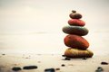 Stones pyramid on sand symbolizing zen harmony balance ocean in the background Royalty Free Stock Image