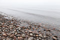 Stones on saimaa lake in foggy morning coast Stock Images