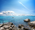 Stony beach clear sea and blue cloudy sky Royalty Free Stock Photos