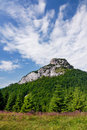 Kamenný vrchol a modrá obloha s mrakmi
