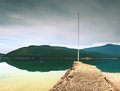 Stony sporty port at mountain lake end of wharf with empty pole without flag dark blue clouds in mirror green water hills Stock Image