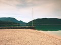 Stony sporty port at mountain lake end of wharf with empty pole without flag dark blue clouds in mirror green water hills Stock Photos