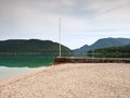 Stony sporty port at mountain lake end of wharf with empty pole without flag dark blue clouds in mirror green water hills Stock Images