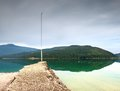 Stony sporty port at mountain lake end of wharf with empty pole without flag dark blue clouds in mirror green water hills Royalty Free Stock Photo