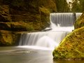 Stony  weir on small mountain river. Stream is flowing over blocks and makes milky water. Royalty Free Stock Photo