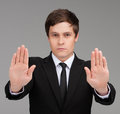 Stop confident young businessman making a sign using hands while isolated on grey Royalty Free Stock Photography