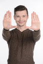Stop gesture cheerful young man showing a sign by his hands while isolated on white Royalty Free Stock Images